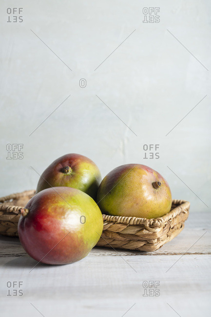 Three ripe mangoes in a wicker basket on a whitewash wood table with bright, natural light.