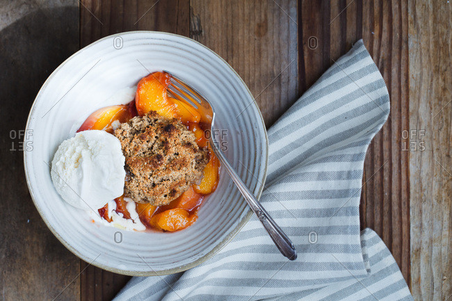Peach cobbler in bowl with ice cream