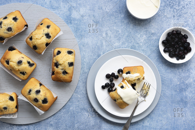 Individual blueberry loaf cakes with a serve on a plate and a bowl of blueberries and a bowl of cream.