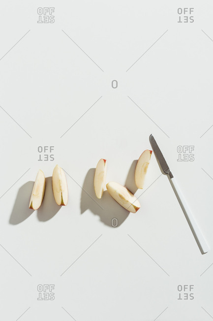 Sliced pieces of apple with knife on white background