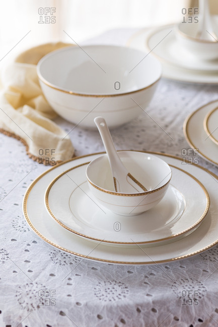 Close-up of white with golden rim bone china with white and gold napkin on a lace tablecloth