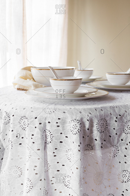 White with golden rim bone china with white and gold napkin on a white lace tablecloth