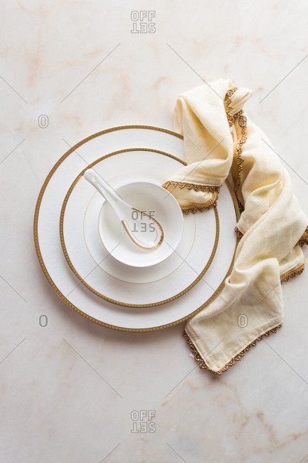 White with golden rim bone china with white and gold napkin on a marble tabletop