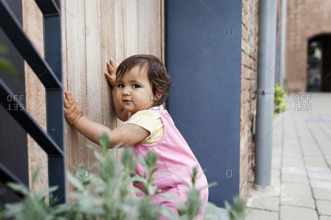 Baby girl leaning against wooden door
