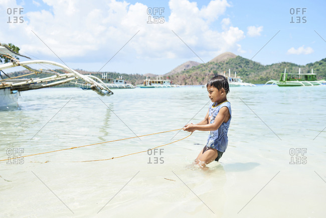 Coron, Philippines - March 19, 2018: Little kid pulling a rope from a watercraft into the water.