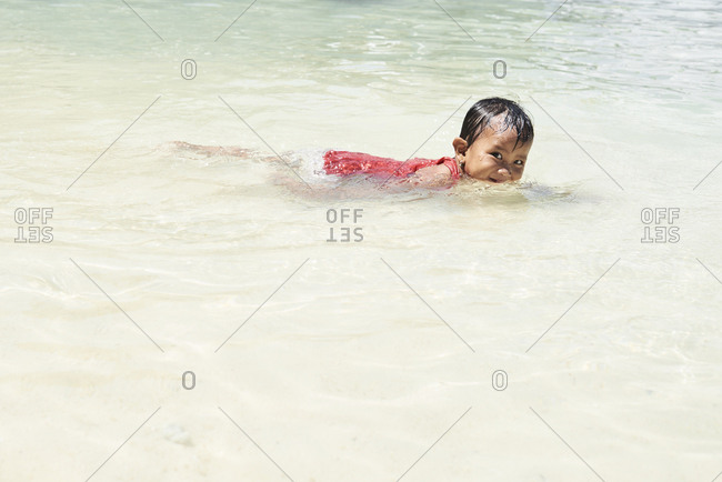 Coron, Philippines - March 19, 2018: Portrait of beautiful girl swimming and  looking naughty at camera.
