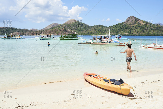 Coron, Philippines - March 19, 2018: Panoramic view of CYC beach in Coron Island in summer with tourists and boats.