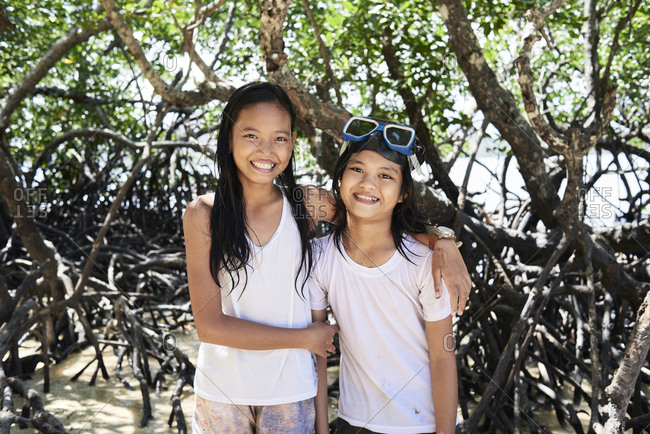 Coron, Philippines - March 19, 2018: Portrait of happy filipino sisters wearing snorkel goggles and smiling at camera.