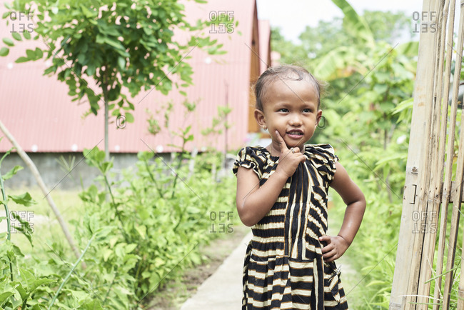 Gili Islands, Indonesia - April 10, 2018: Cute indonesian little girl thinking like an adult with finger on cheek.