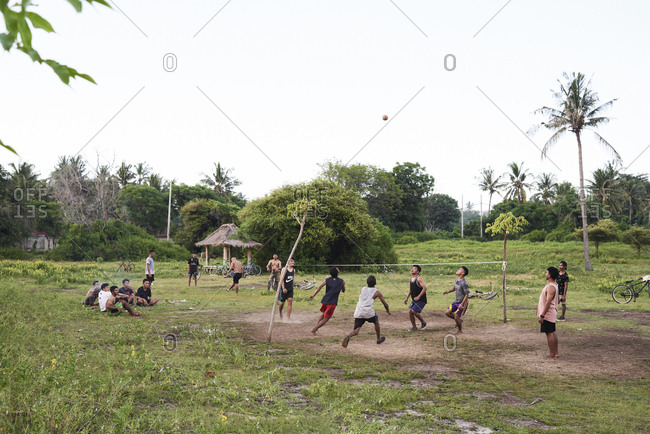 Gili Islands, Indonesia - April 11, 2018: Group of friends playing volleyball in a palm tree forest in summer.