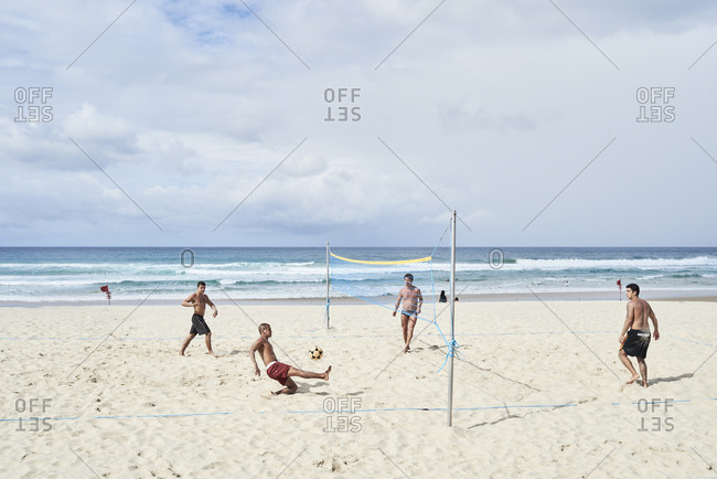 Gold Coast, Australia - April 28, 2018: Group of brazilian friends playing futvolley at the surfers beach.