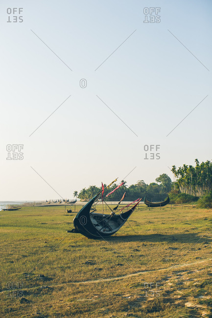 Traditional wooden boat lying on its side on river bank in Bangladesh