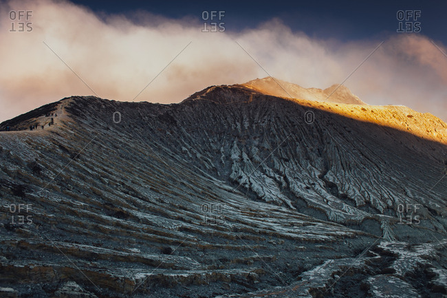 Climbers walking along craggy ridge in volcanic landscape of Mount Bromo