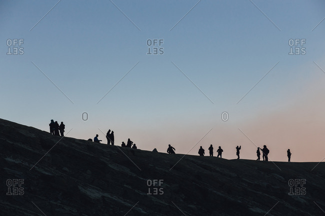 Travelers silhouetted on a ridgeline as they climb Mount Bromo