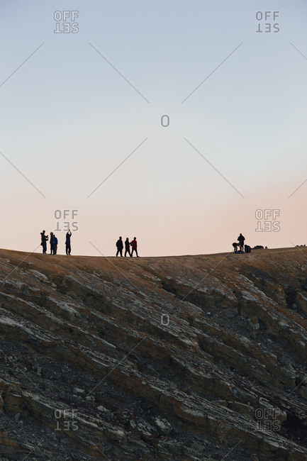Silhouettes of climbers as they walk along ridge on Mount Bromo