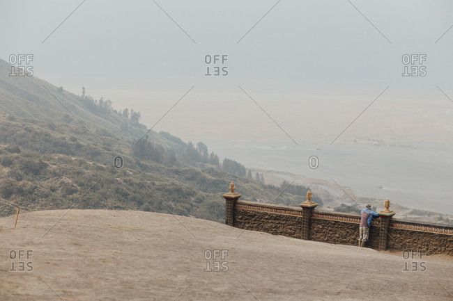 Rearview of man looking over wall on hillside into hazy valley