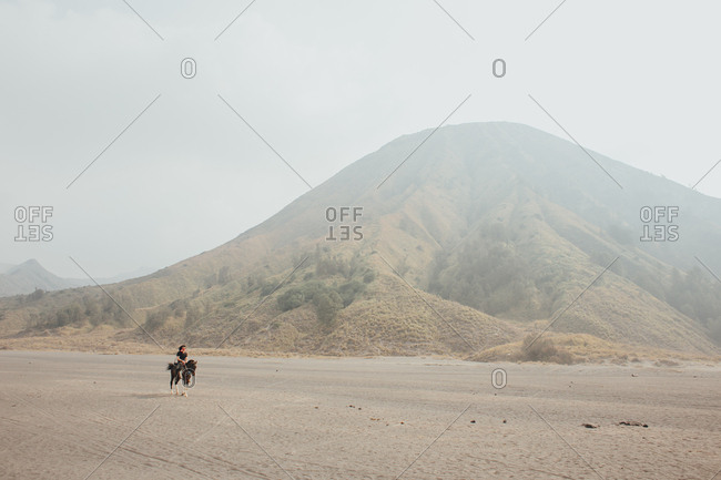 Single rider on horseback travelling through barren sandy terrain with hills in background