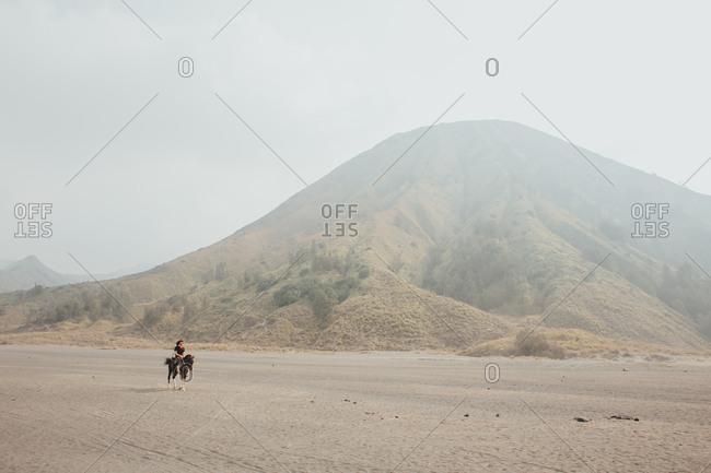 Single rider on horseback travelling through barren sandy terrain with hills in background