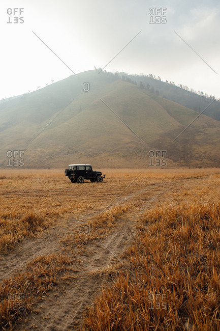 Off road vehicle parked off track with hills in background