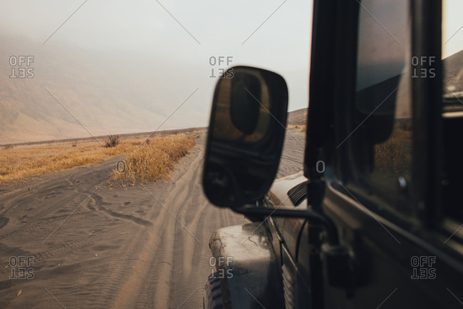 View out of window of all terrain vehicle travelling on sandy track in mountainous environment