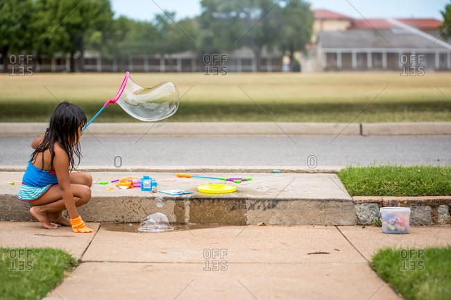 Girl playing with soapy bubbles on sidewalk