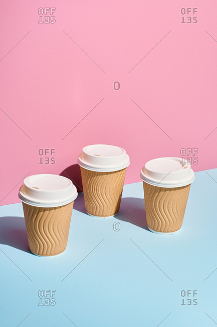 Disposable coffee cups on pastel background
