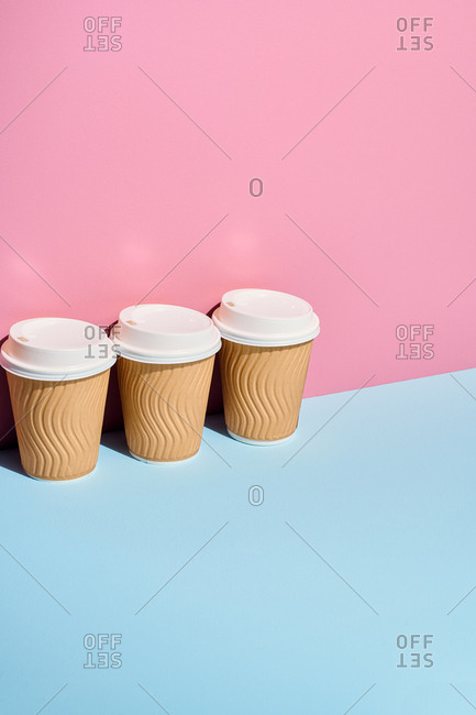 Cardboard coffee cups on pastel background