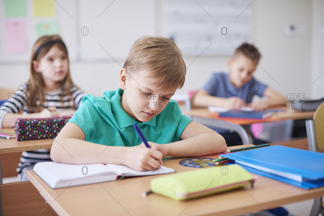 Schoolboy writing in exercise book in class