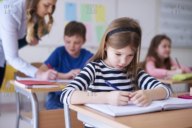 Schoolgirl writing in exercise book in class