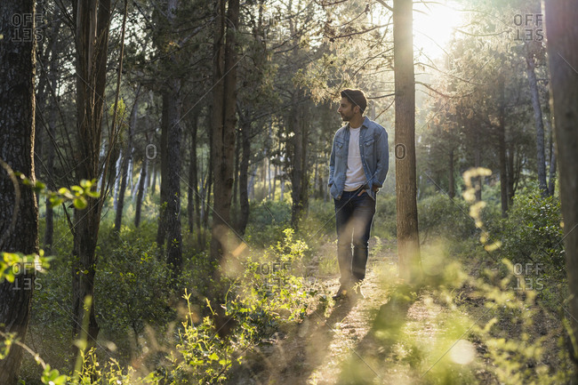 Young man standing in forest- against the sun