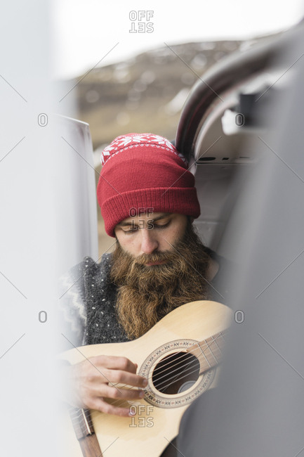 Portrait of hipster wearing red woolly hat playing guitar