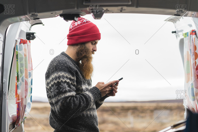Hipster standing at van using cell phone