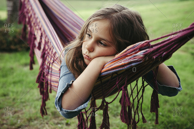 Portrait of sad girl lying in hammock