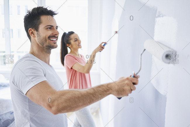 Happy couple painting wall in apartment together