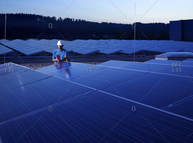 Worker with measuring device checking solar plant in the evening