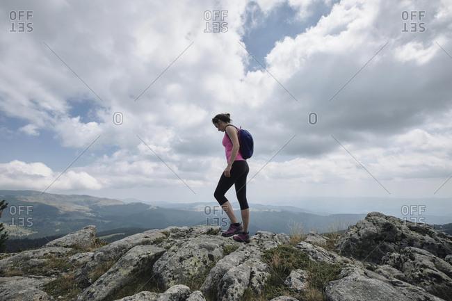 Bulgaria- Rila Mountain- female hiker standing on cliff edge