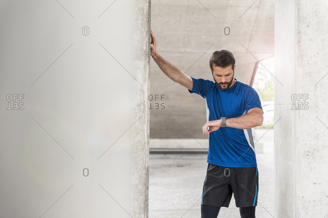 Man having a break from running checking the time