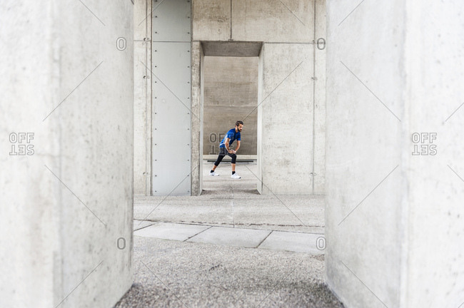 Man stretching at an underpass