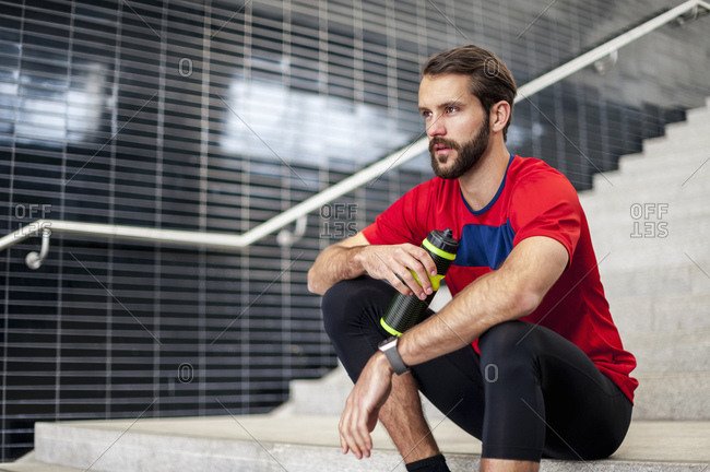 Man sitting on stairs having a break from running