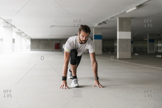 Athlete in starting position in parking garage