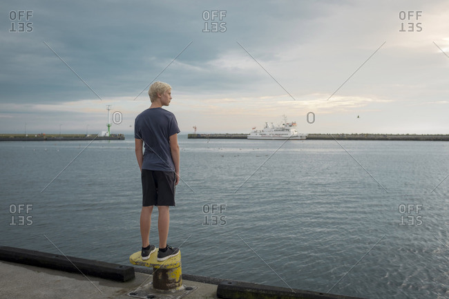 Poland- Gdansk Bay- teenage boy standing on quay looking at distance