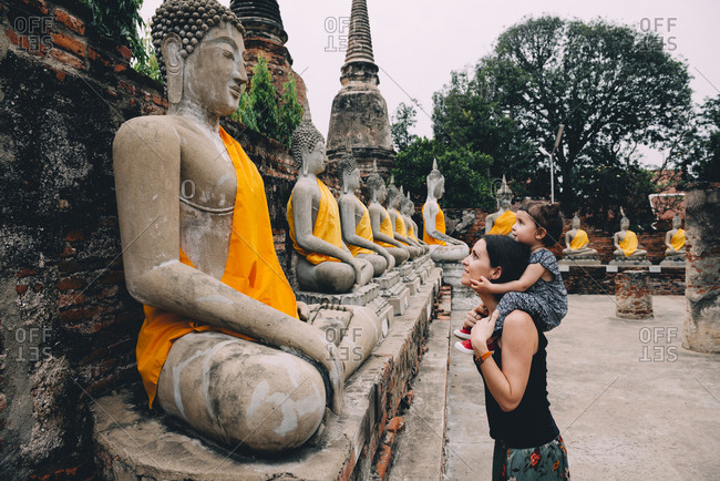 Thailand- Bangkok- Ayutthaya- Buddha statues in a row in Wat Yai Chai Mongkhon- mother and daughter in front of a buddha statue