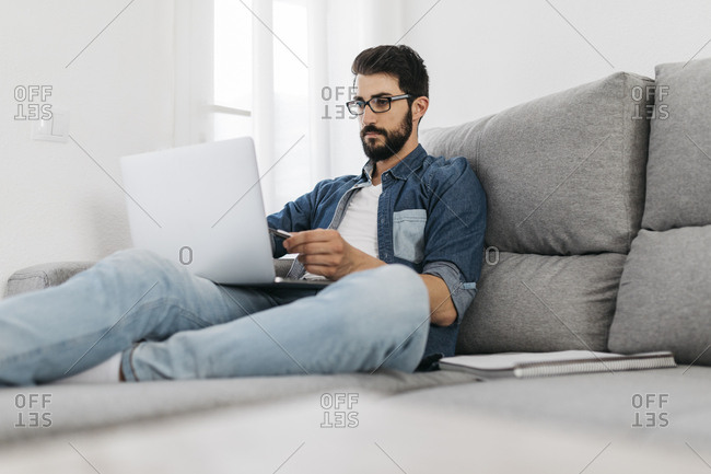 Man using laptop- working on the couch at home