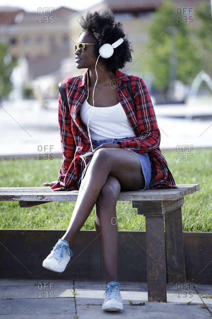 Portrait of young woman sitting on bench in city park listening music with headphones