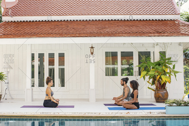 Two women and a man practicing yoga at the poolside
