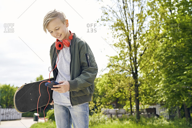 Boy with headphones and skateboard using smartphone