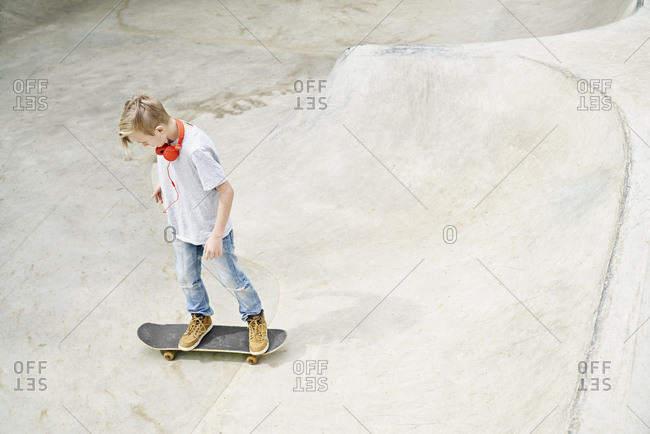 Boy with headphones on skateboard- skateboarding