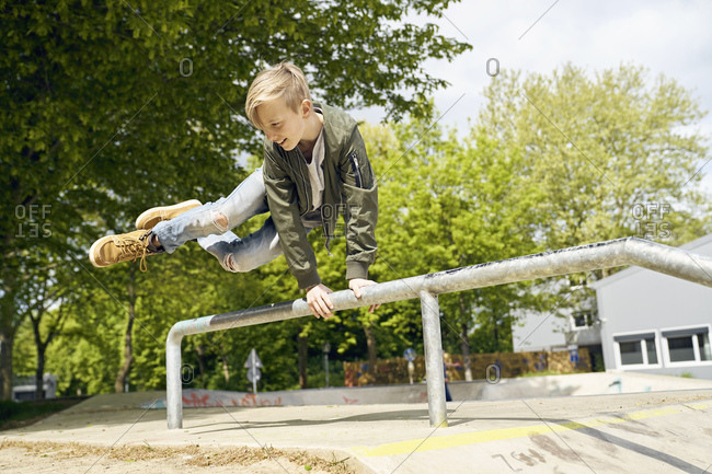 Boy jumping over railing in skatepark