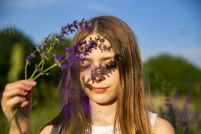Portrait of girl with purple blossom at evening twilight