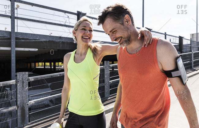 Fit couple jogging in the city- having fun- taking a break